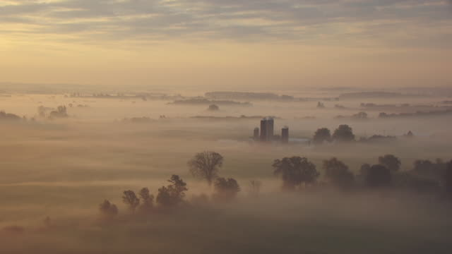WS AERIAL View of farm with grain elevators during sunrise with morning mist in the fields in Dodge County / Wisconsin, United States