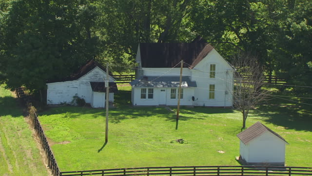 WS AERIAL POV View of farmhouse and outbuildings with trees and fence / Orange County, French Lick, Indiana, United States