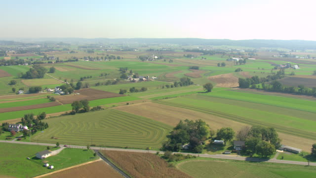vídeos de stock e filmes b-roll de ws aerial view of farmland and houses with silos in amish countryside / pennsylvania, united states - amish