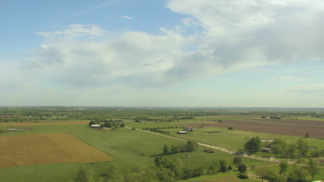 stockvideo's en b-roll-footage met ws aerial view of farmland under big sky with car moving on countryside road in jefferson county / kansas, united states - kansas