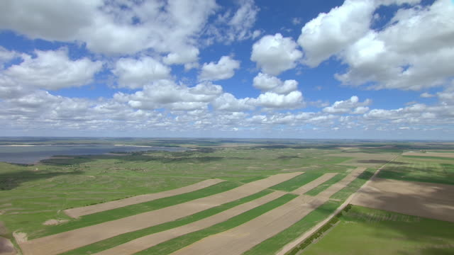 WS AERIAL View of Farmland under fluffy clouds in sky approaching Lake McConaughy / Nebraska, United States