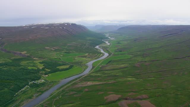 vídeos de stock e filmes b-roll de ws aerial view of farmland valleys with river at akureyri town / iceland - vale