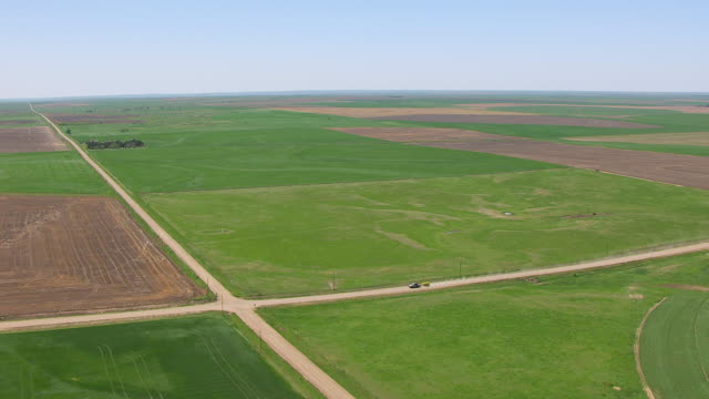 vídeos de stock e filmes b-roll de ws aerial view of farmland with car moving on dirt road in kiowa county / kansas, united states - kansas