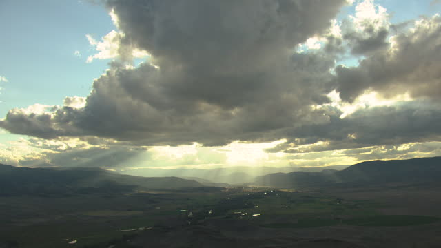 ws aerial view of farmland with hills and rain clouds with sunbeams shining through clouds during sunset in saguache county / colorado, united states - ドラマチックな空模様点の映像素材/bロール