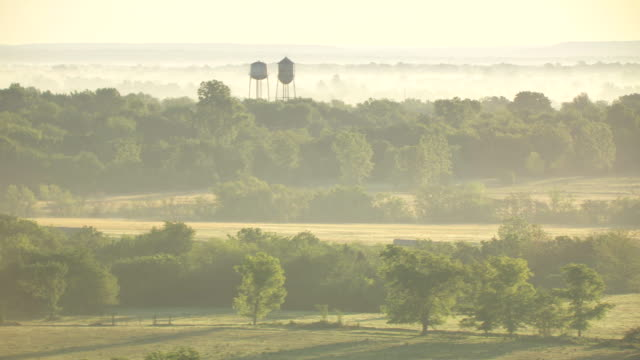 ws aerial view of farmland with mist in air and water storage tanks  / oklahoma, united states - oklahoma stock-videos und b-roll-filmmaterial