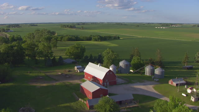 ws aerial pov view of farmland with silos / hardin county, iowa, united states - barn stock videos & royalty-free footage