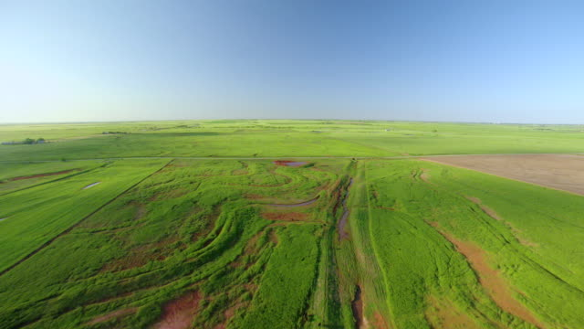 vidéos et rushes de ws aerial view of farmland with sunlight on wheat fields in garfield county / oklahoma, united states - plaine caractéristiques de la terre