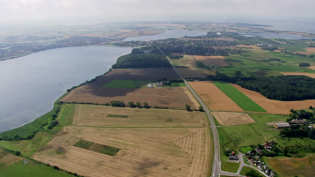 ws aerial zi view of farms, highway and houses / vestsjaelland, denmark - smoke stack stock videos & royalty-free footage