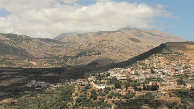 WS T/L View of fast motion of clouds over mount Hermon and Arab village / Golan Heights, Israel