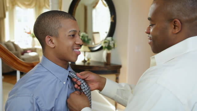 MS View of father helping to son tie necktie / Albany, New York, United States