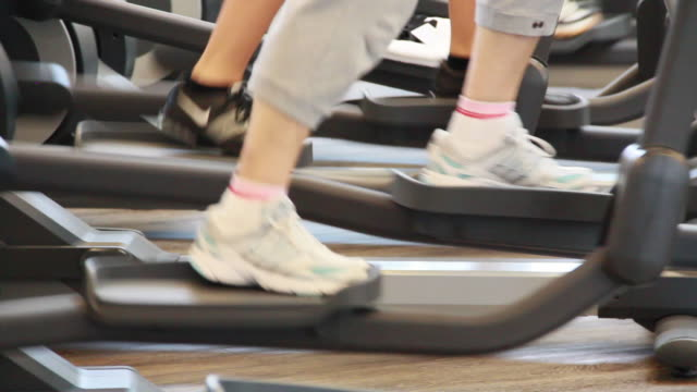 ms view of feet in sport shoes are walking on elliptical machines / neumarkt, bavaria, germany - cross trainer stock videos and b-roll footage