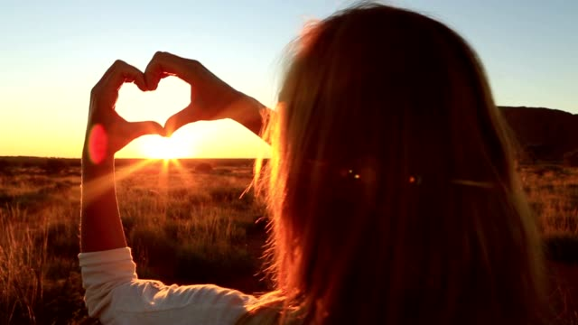 view of female framing sunset into heart shape - northern territory australia stock videos & royalty-free footage