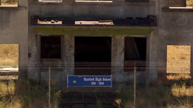 ms aerial tu view of fence with sign of abandoned hanford high school building at hanford site / richland, washington, united states - hanford nuclear reservation video stock e b–roll