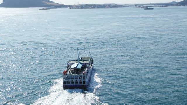 view of ferry boat sailing into seongsan harbor in jeju island, south korea - ferry stock videos & royalty-free footage