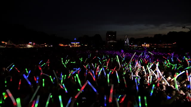 ws cs pov view of festival crowd with giant glow sticks at night / victoria park, london, united kingdom - victoria park london stock videos & royalty-free footage