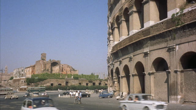 ms pan view of  few cars passing in front of coliseum / rome, italy   - 1960 stock-videos und b-roll-filmmaterial