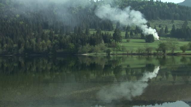ws, ha, view of fields across lake bohinj, smoke rising from field, triglav national park, gorenjska, slovenia - triglav national park stock videos and b-roll footage