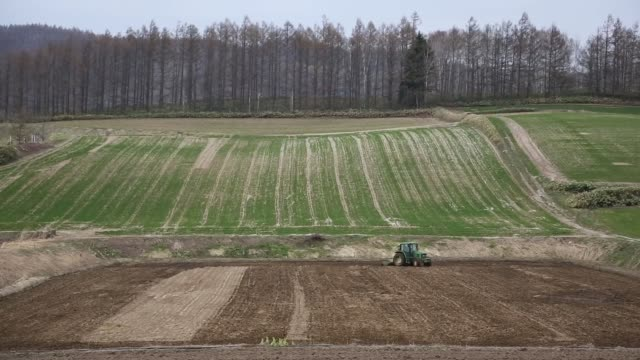 a view of fields in the countryside of western hokkaido is seen from a moving train long shot a farmer on a tractor plows soil in nakafurano town... - kamikawa subprefecture stock videos and b-roll footage