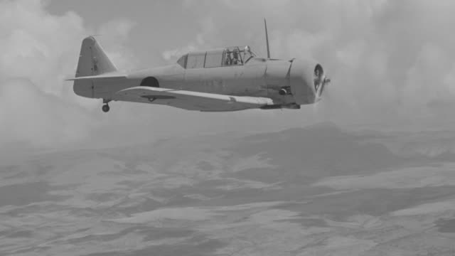 ws aerial view of fighter plane in flight from left to right above clouds - flugzeug in der luft stock-videos und b-roll-filmmaterial