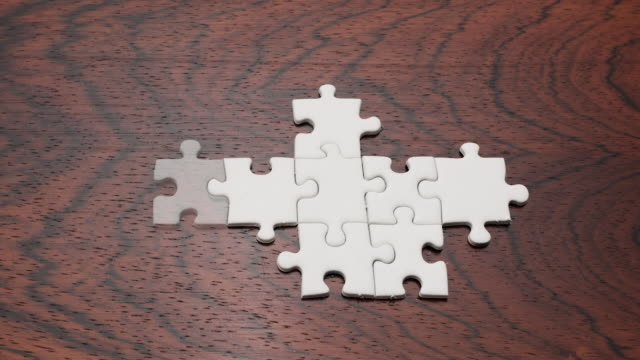 stockvideo's en b-roll-footage met cu zo view of finishing puzzle against wooden background / germany - puzzel