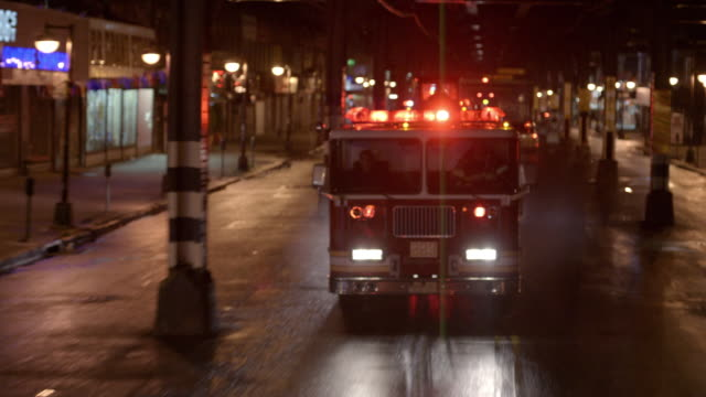 vídeos de stock e filmes b-roll de rear pov, view of fire truck driving on street at night, new york city, new york, usa - carro de bombeiro