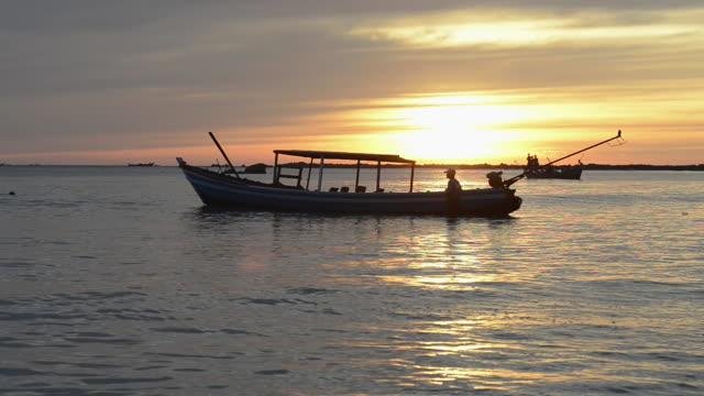 ws view of fisherman in boat on sea at sunset / ngapali, rakhine state, myanmar - 男漁師点の映像素材/bロール