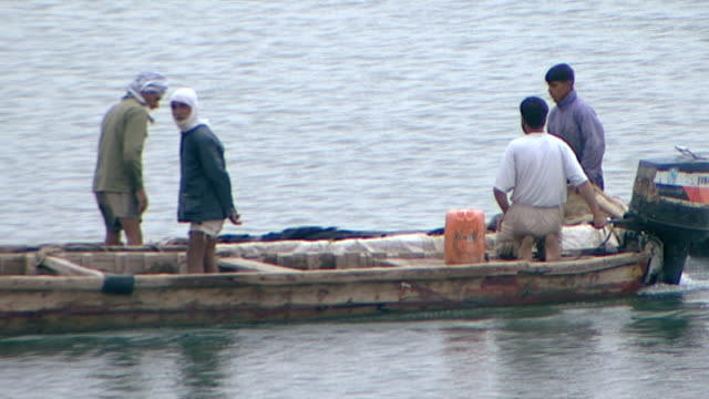 view of fishermen in a motorboat throwing their net into shatt al-arab. the river is formed by the confluence of the euphrates and tigris and runs... - basra stock-videos und b-roll-filmmaterial