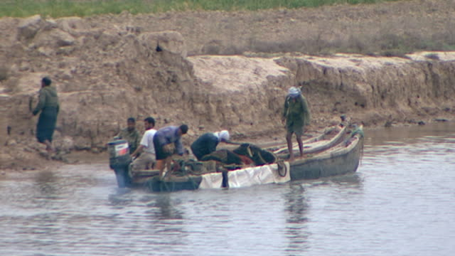 view of fishermen leaving the shore of shatt al-arab in a motorboat. the river is formed by the confluence of the euphrates and tigris and runs into... - ペルシャ湾点の映像素材/bロール
