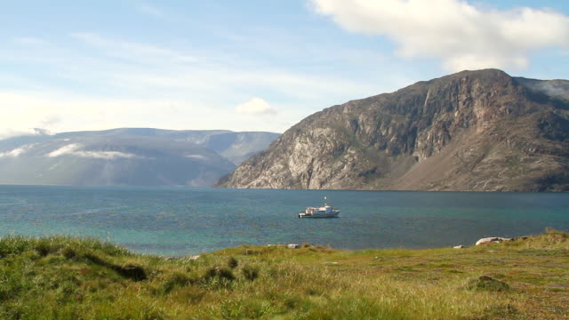 stockvideo's en b-roll-footage met ws view of fishing boat in clear blue water with mountains and grass field / torgat mtns, labrador, canada - wiese