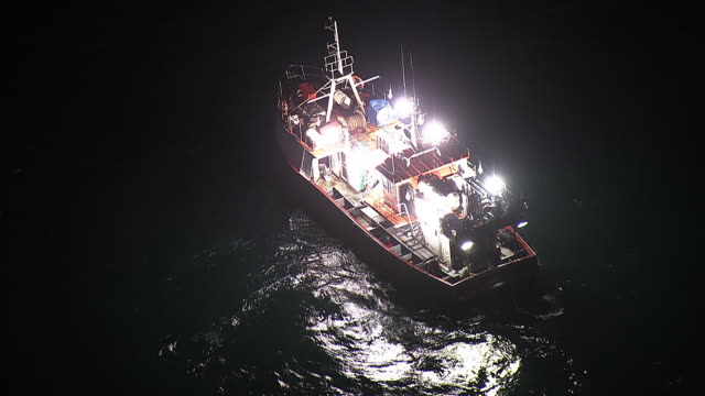 MS AERIAL View of fishing trawler at sea at night / Port Elizabeth, Eastern Cape, South Africa