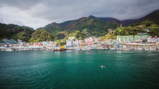 vídeos de stock e filmes b-roll de ws t/l view of fishing village and mountains nearby jeodonghang harbor with boats moving in sea / ulleung, gyeongsangbuk do, south korea - aldeia de pescador