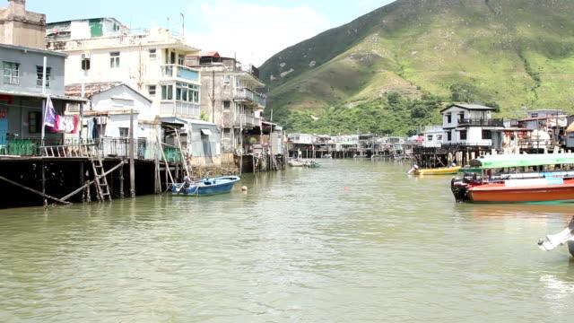 vídeos de stock e filmes b-roll de view of fishing village with bridge at distant while motorboat passing through river at tai o, hong kong, china - aldeia de pescador