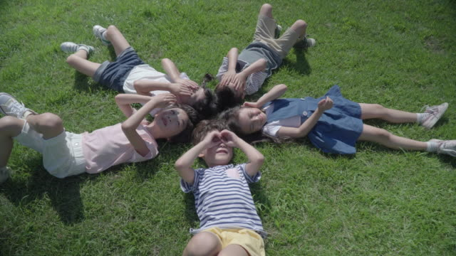 View of five children lying down on the lawn with smile in summer at Seoulforest (the third largest park in Seoul city)