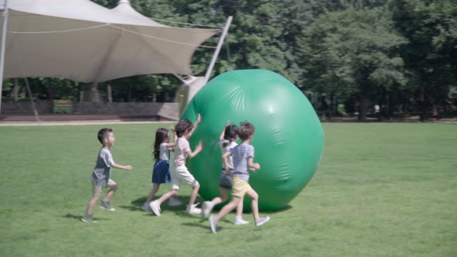 view of five children rolling a huge gym ball in summer at seoulforest (the third largest park in seoul city) - fitness ball stock videos & royalty-free footage