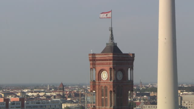 view of flag waving with wind on top of red town hall(rotes rathaus) and television tower against skyline of berlin - rathaus点の映像素材/bロール
