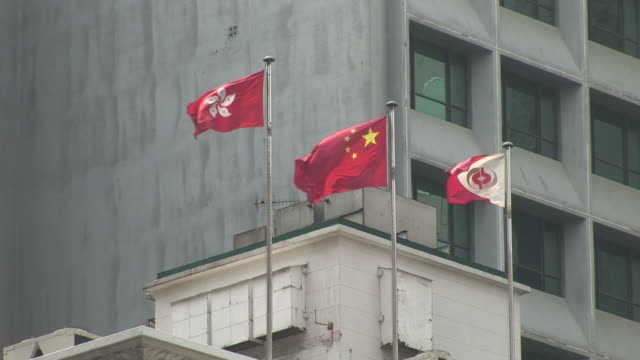 view of flags flapping in the wind in hong kong china - chinese flag stock videos & royalty-free footage