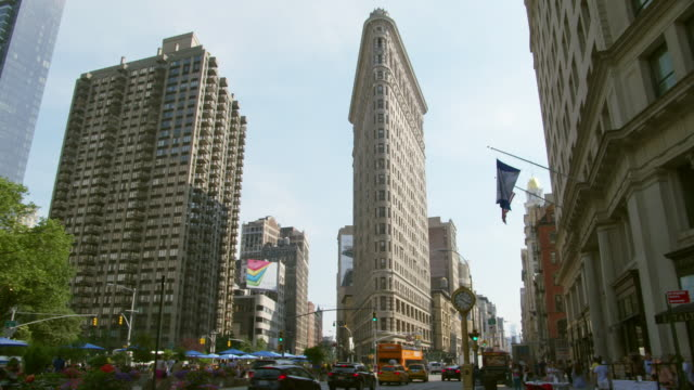 ms view of flat iron building with cars and pedestrians / new york, united states - flatiron building manhattan stock videos and b-roll footage