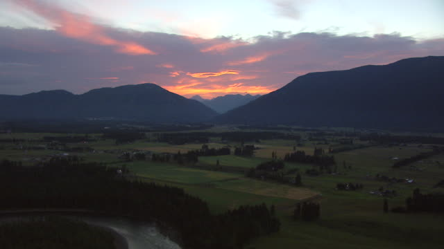 WS AERIAL View of Flathead River with farms in during sunrise / Montana, United States