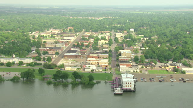 WS AERIAL View of flooding riverfront and downtown buildings with farm land / Greenville, Mississippi, United States