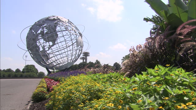 ws view of flushing meadows corona park with garden in foreground and plane taking off in background / queens, new york, usa - flushing meadows corona park stock videos & royalty-free footage