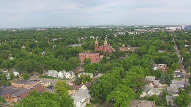 WS AERIAL TD View of Fly over buildings and houses and church / Grand Forks, North Dakota, United States