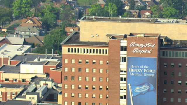ms aerial view of fly past henry ford hospital toward suburban homes / detroit, michigan, united states - henry ford stock videos and b-roll footage