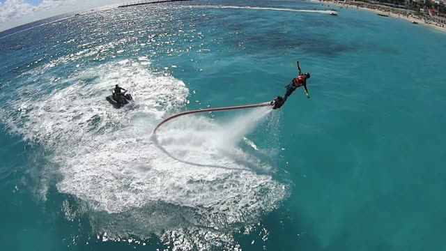 WS AERIAL TS View of Flyboarding in Playa Del Carmen beach / Playa DelCarmen, United States