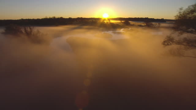 WS AERIAL View of flying through mist towards sun rising on horizon in Dane County / Wisconsin, United States