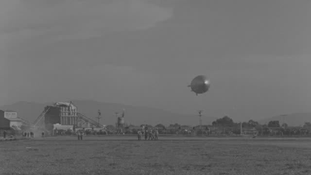 WS View of flying Zeppelin over open landscape
