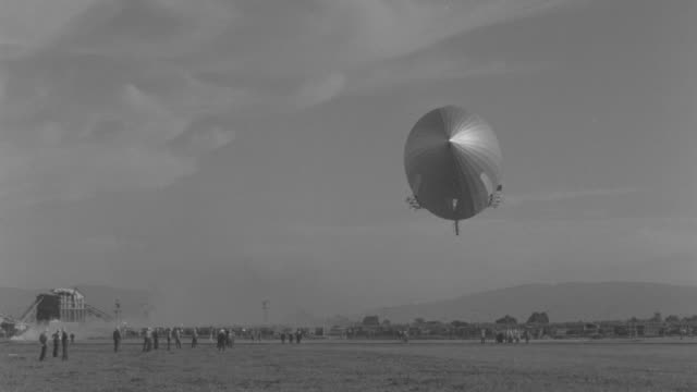 WS View of flying Zeppelin over open landscape