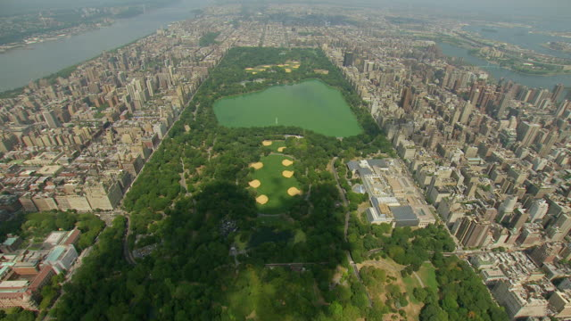 ws aerial view of flyover central park with golf course and lake with buildings surrounding park in manhattan / new york, united states - central park manhattan video stock e b–roll