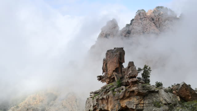 ms view of fog moves over fantastic rocks of calanche of piana, unesco world heritage site / porto, corsica, france - igneous stock videos & royalty-free footage