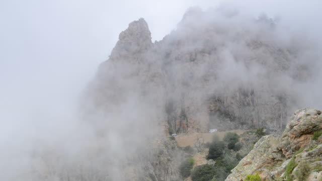 ws view of fog moves over mountains of calanche of piana, unesco world heritage site / porto, corsica, france - ピアナ点の映像素材/bロール