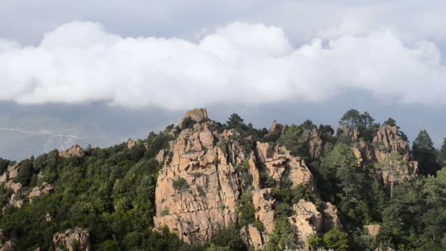 ws view of fog over mountains of calanche of piana, unesco world heritage site / porto, corsica, france - カランシェ点の映像素材/bロール